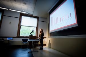 Female student giving presentation illustrated with column histogram