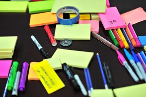 Photo of sticky notes, colored pens, and markers scrambled on table. Photo by Frans Van Heerden (Canva).
